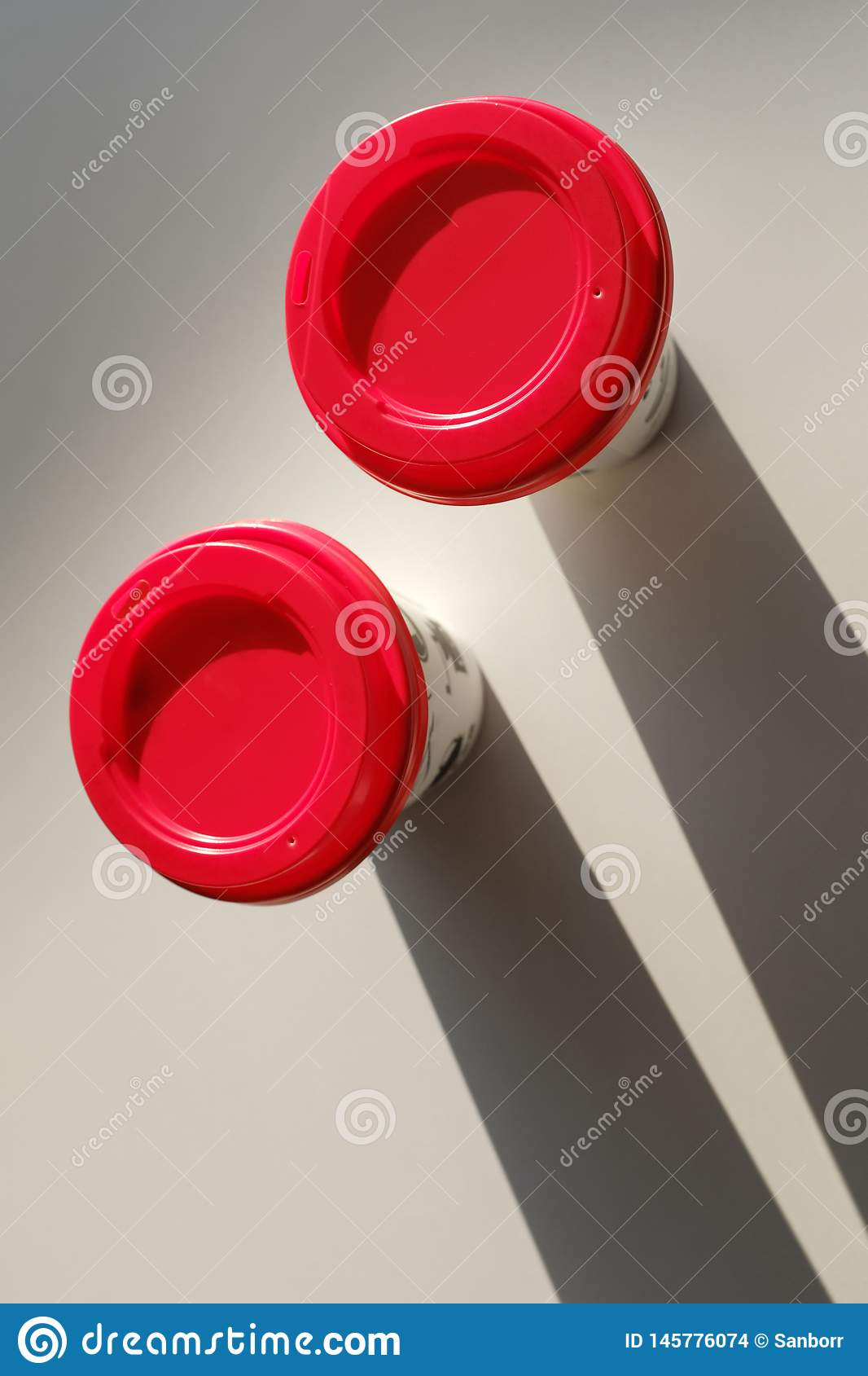 2 boxes of paper disposable cups with a red lid on the table in the cafe. Coffee to go. Morning. Coffee for Breakfast. 2 cups of