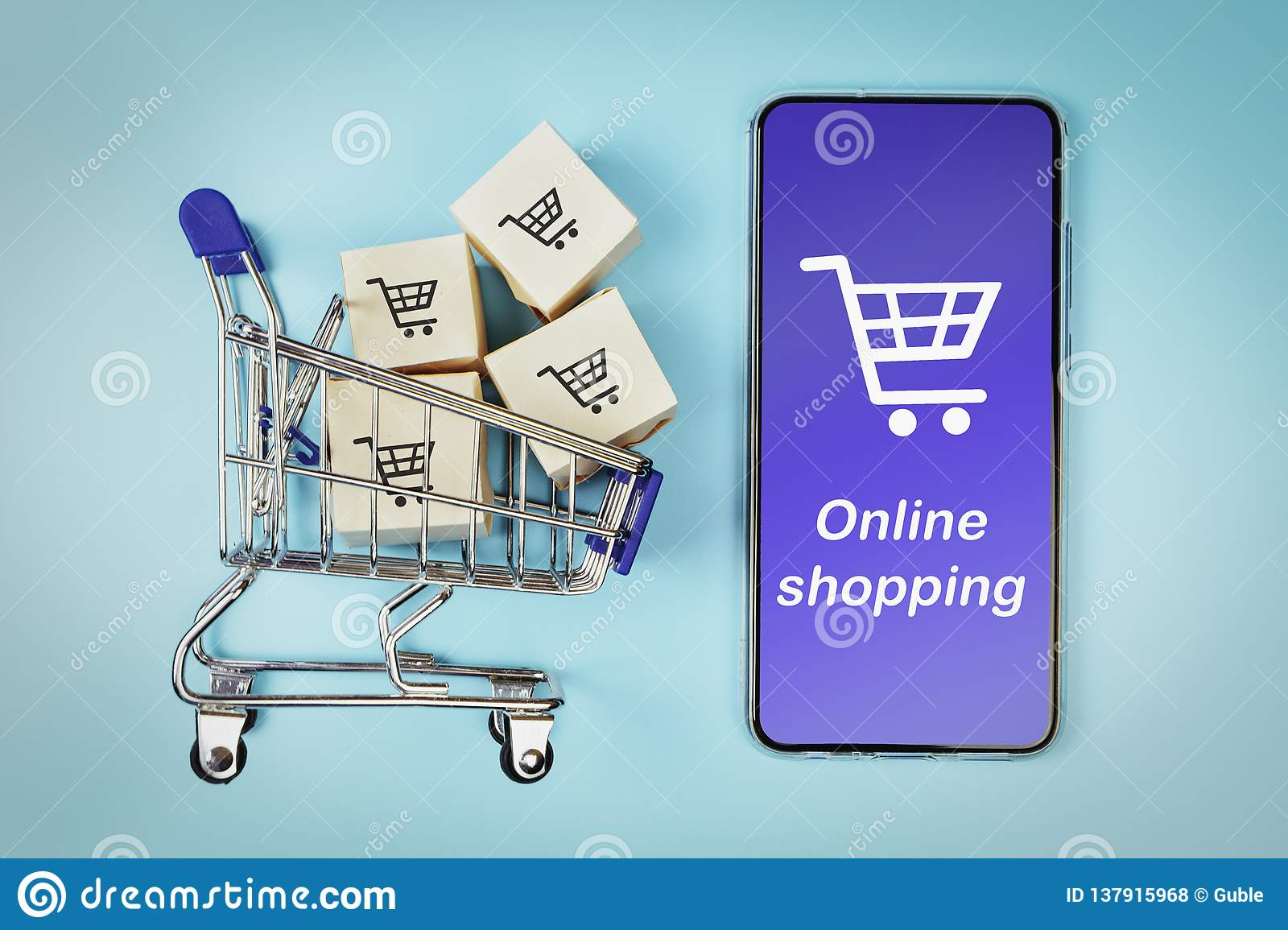 Boxes in a shopping cart and smartphone on blue background. Concept: online shopping, e commerce and delivery of goods