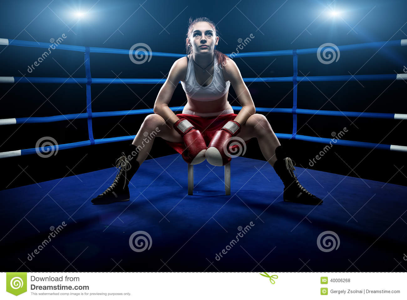Boxing woman sitting alone in the boxing arena , surrounded by blue lights