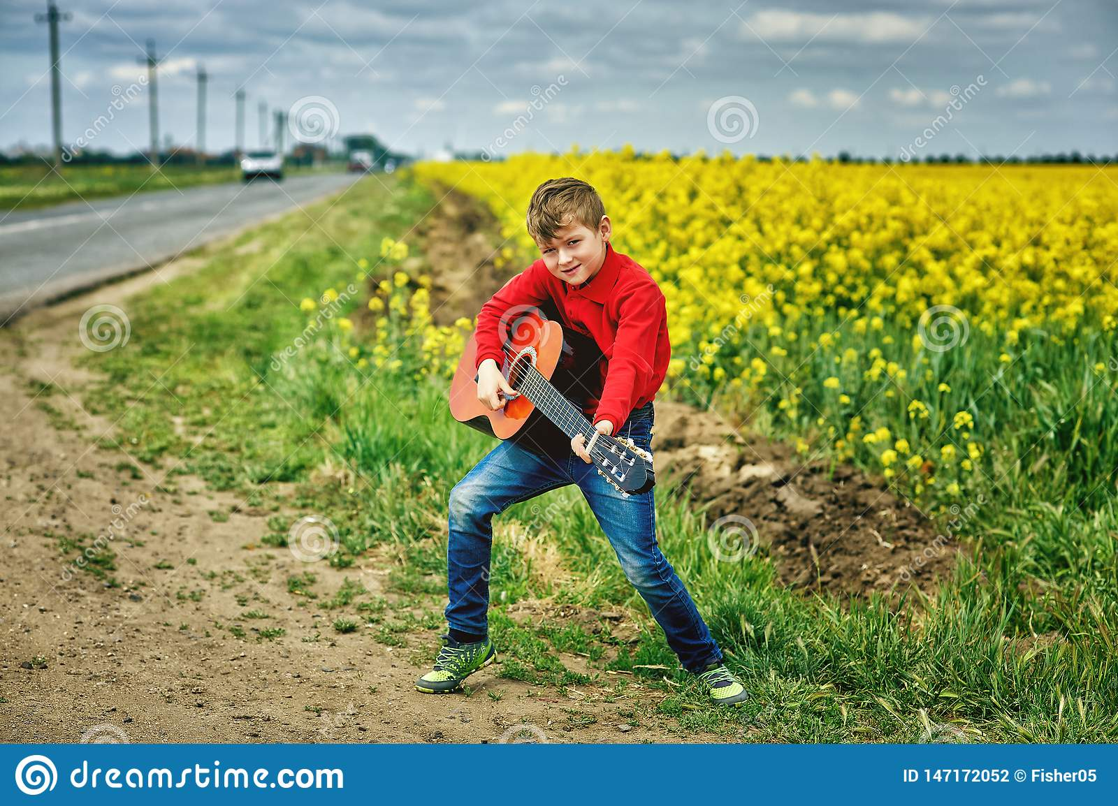Boy with acoustic guitar outdoors