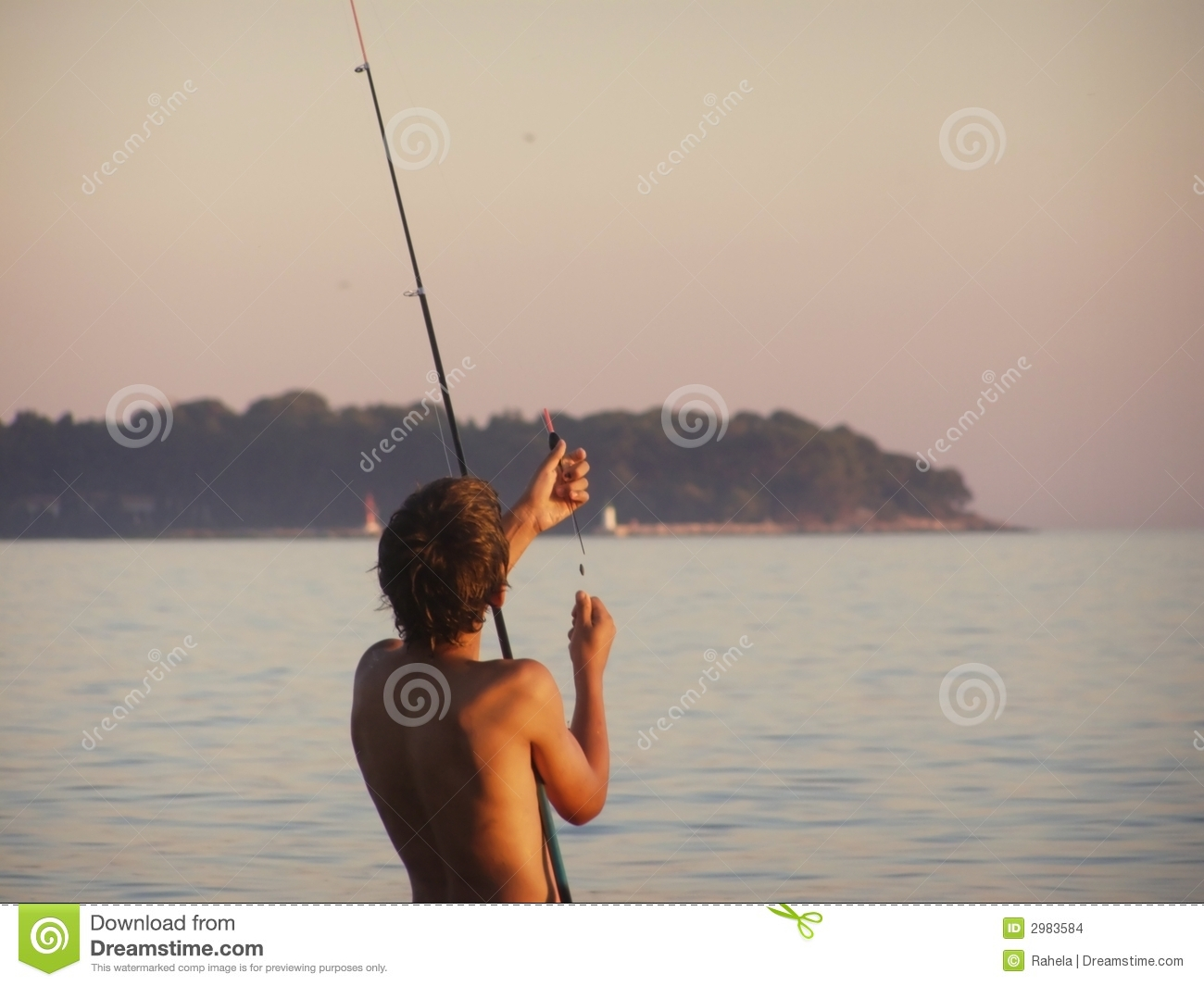 Boy angling at sunset