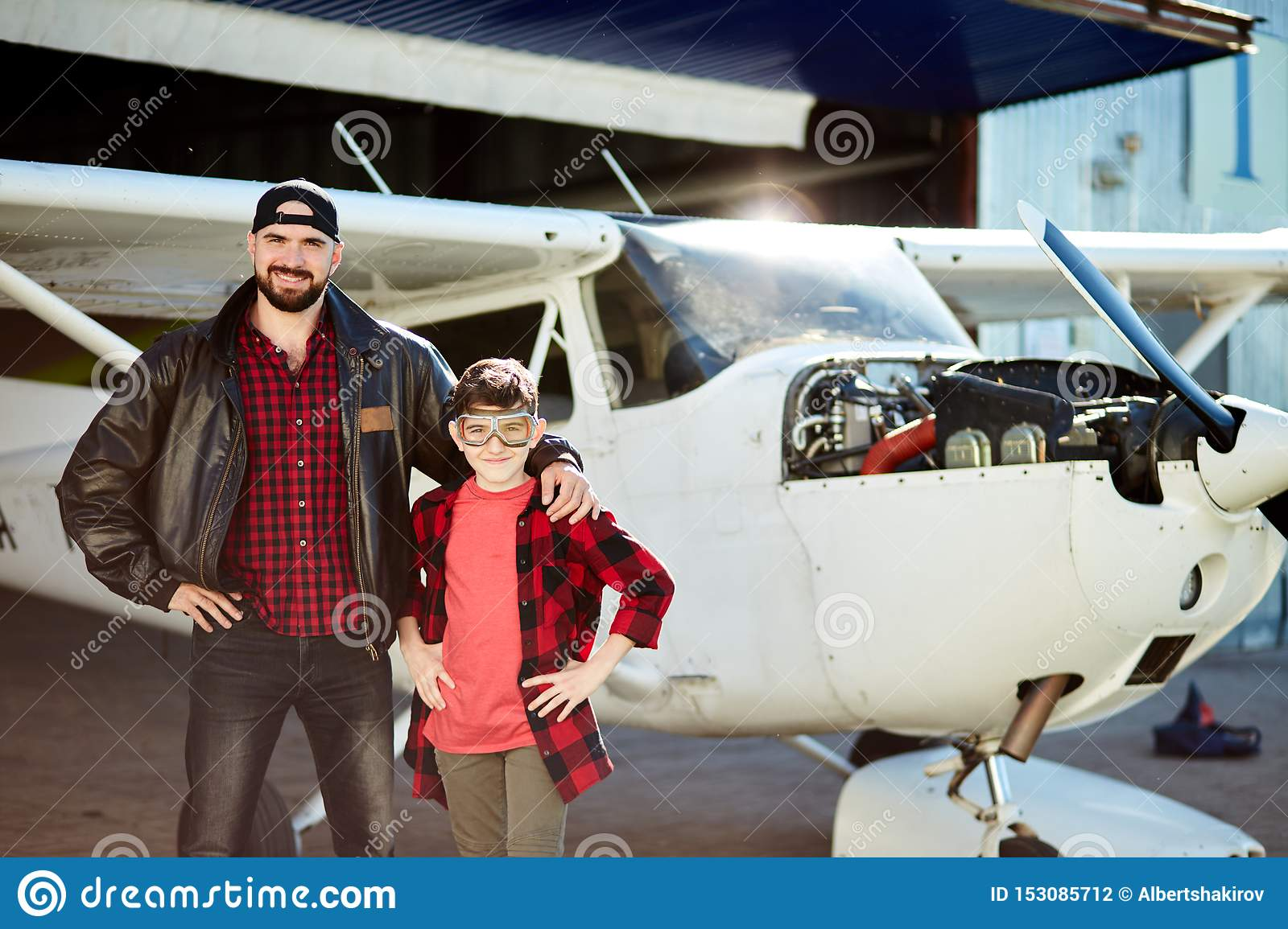 Boy in aviator glasses feels glad his father took him to hangar where he makes repair works