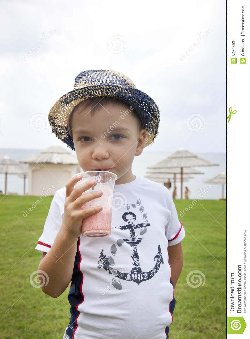 Boy on the beach drinking cocktail