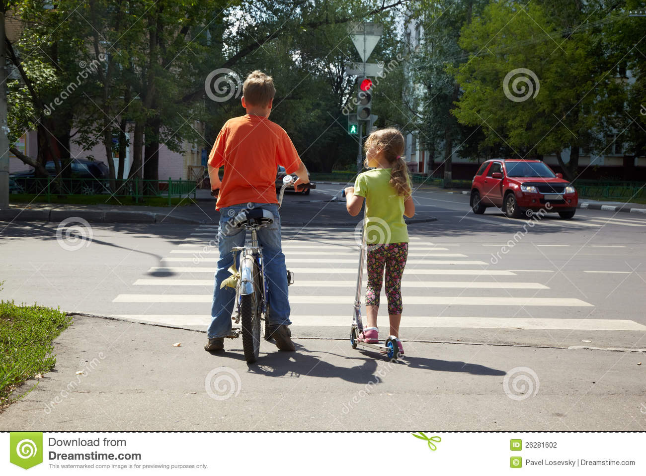 Boy with bicycle and his sister with scooter stand
