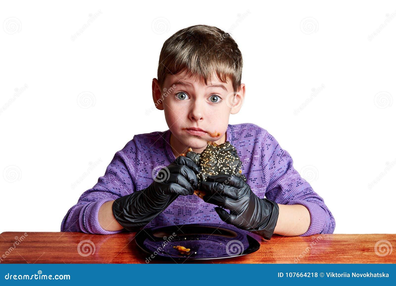 Boy in black gloves emotionally eating a burger