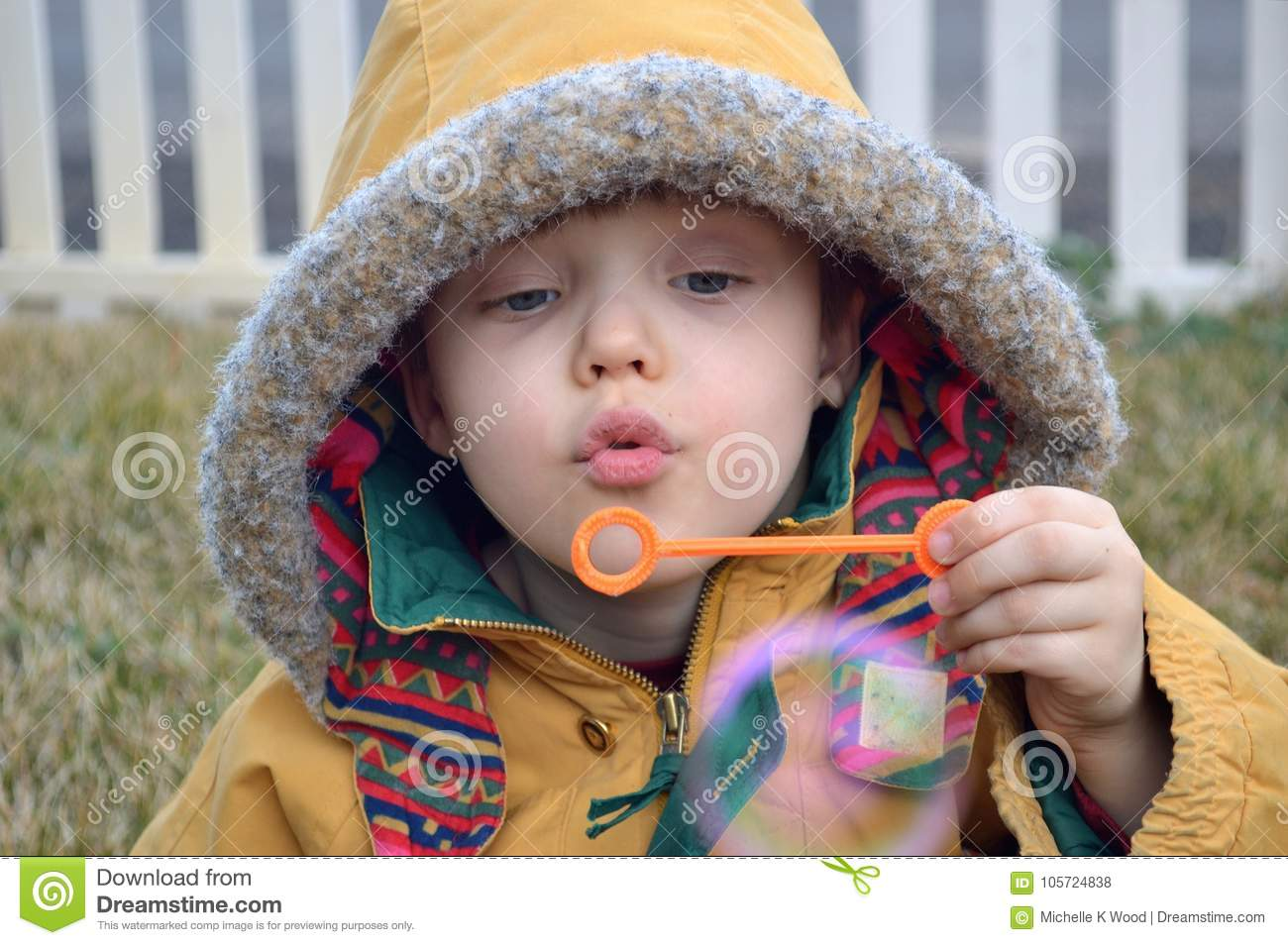 Boy blowing bubbles in the winter