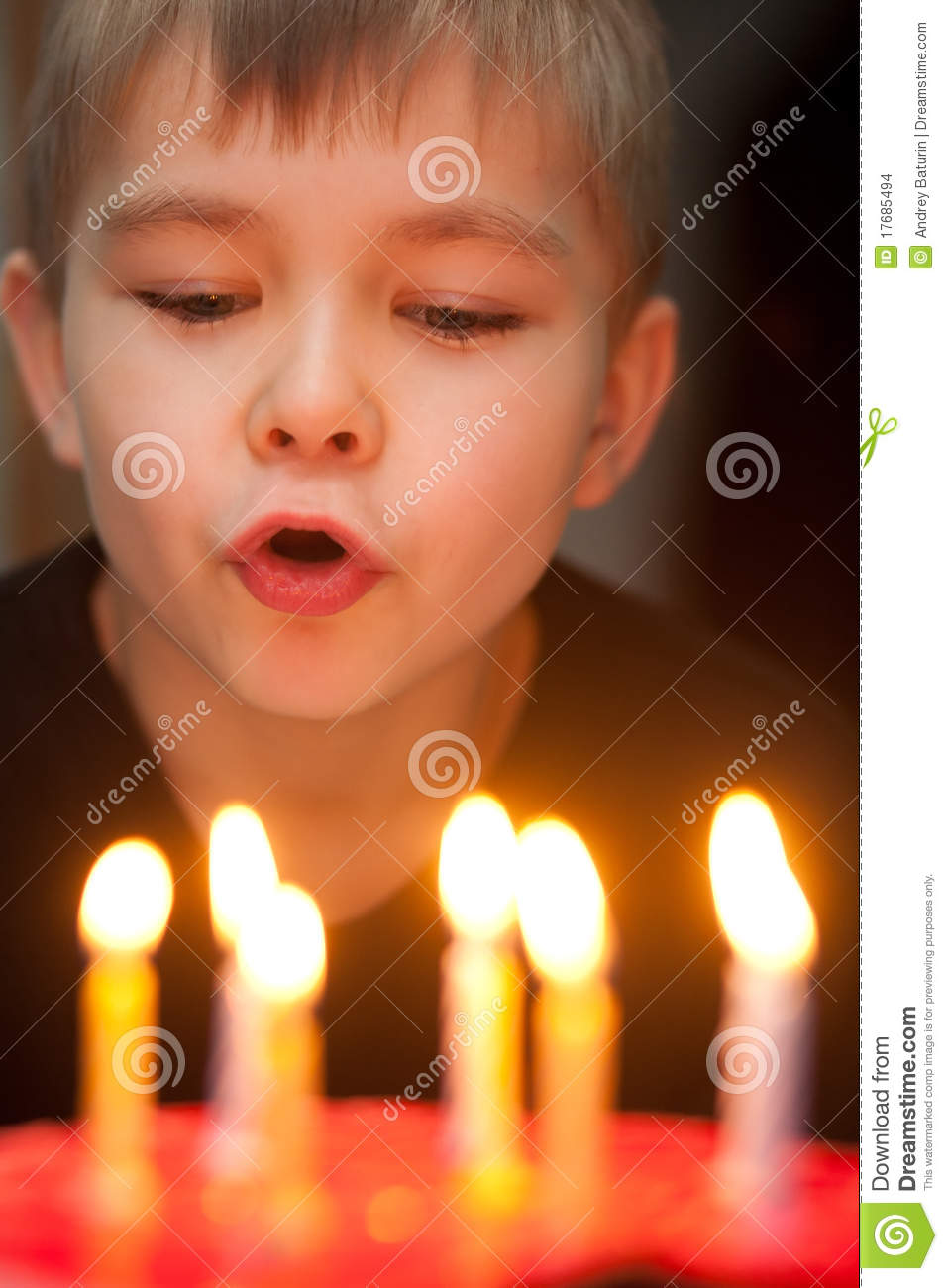Boy Blowing Out Candles On Birthday Cake Stock Photo