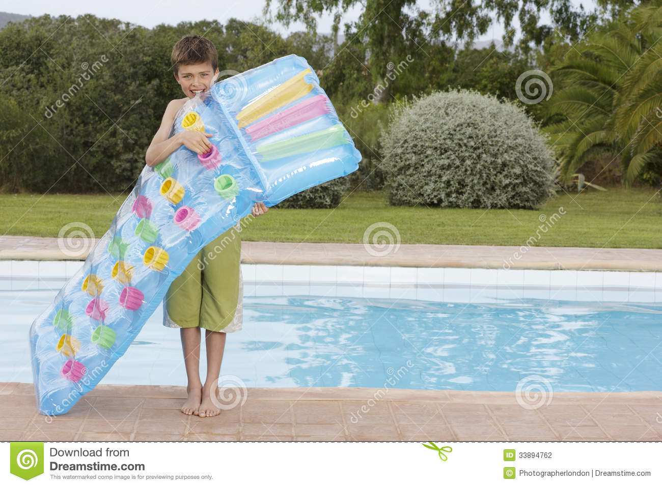 Boy Blowing Up Air Mattress Against Pool Stock Photo