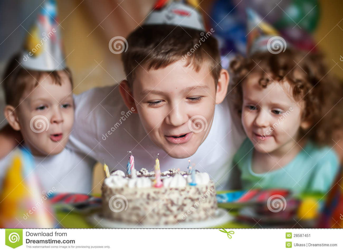 boy blows out the candles on a birthday cake and hugs his brother and sister