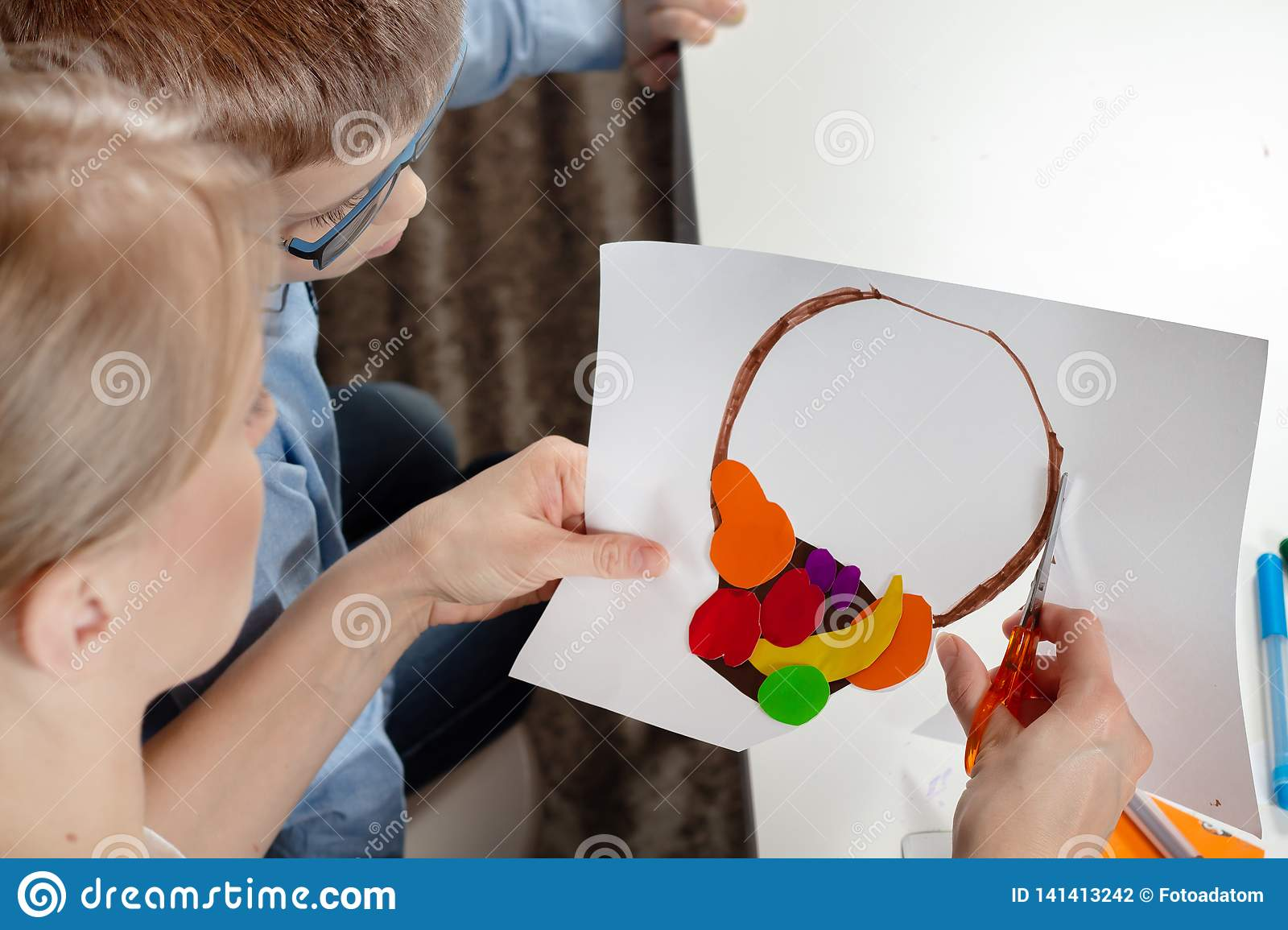 Boy in a blue shirt with mum. The boy`s mom cuts scissors with a plastic work done by a child.