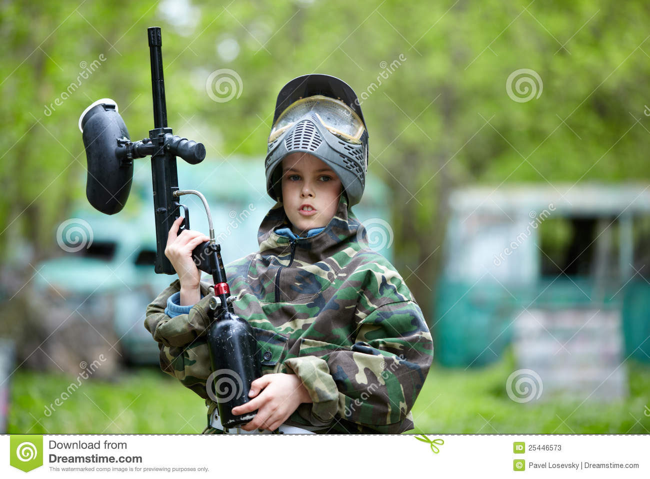 Boy In Camouflage Holds A Paintball Gun Barrel Up Stock