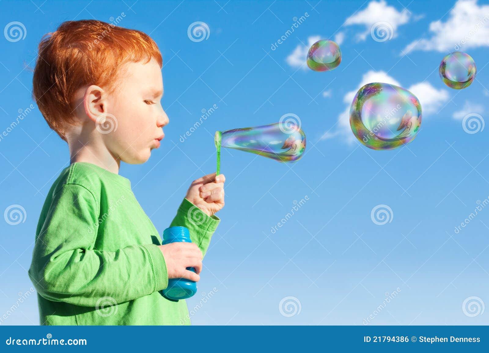 Boy child blowing soap bubbles into sky