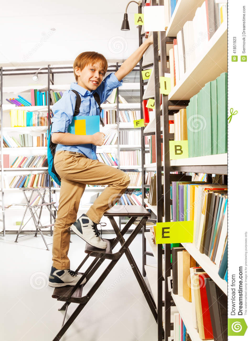 Boy Climbing On Step Ladder In Library Stock Image - Image ...