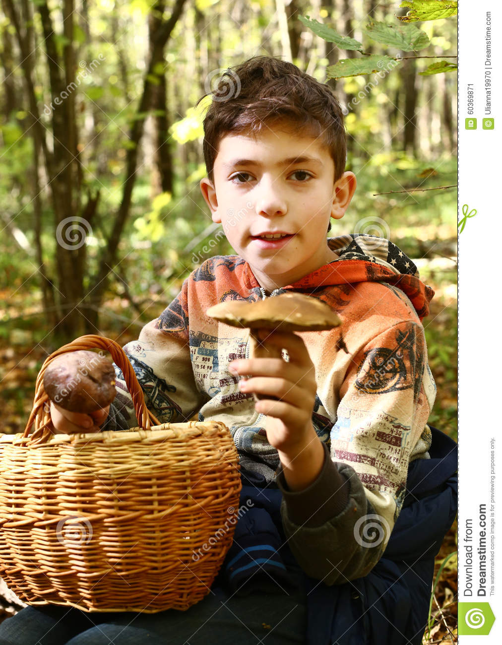 Boy collect mushrooms in the autumn forest