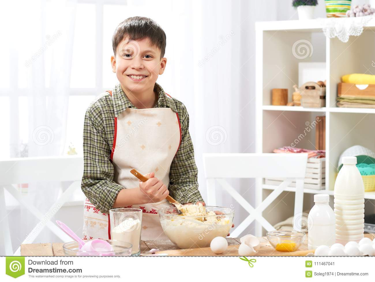 Boy cooking at home, making dough, buns and cookies