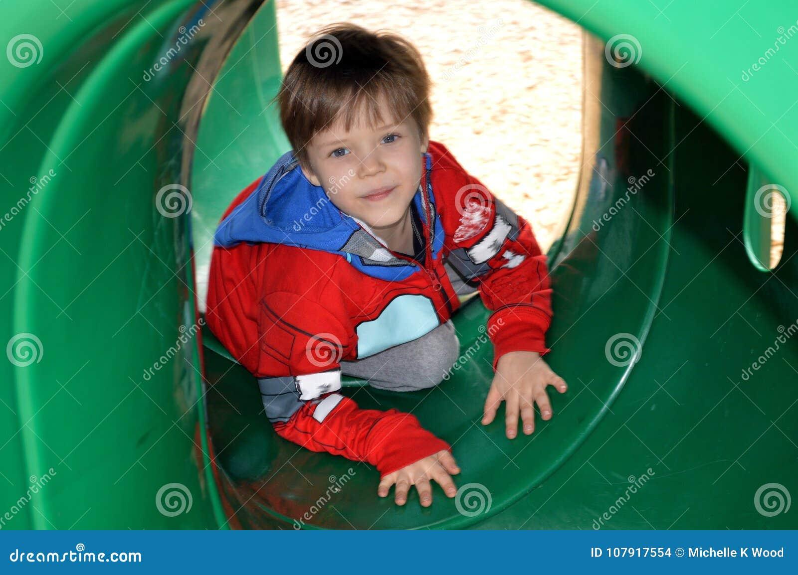 Boy crawling through a playground tunnel