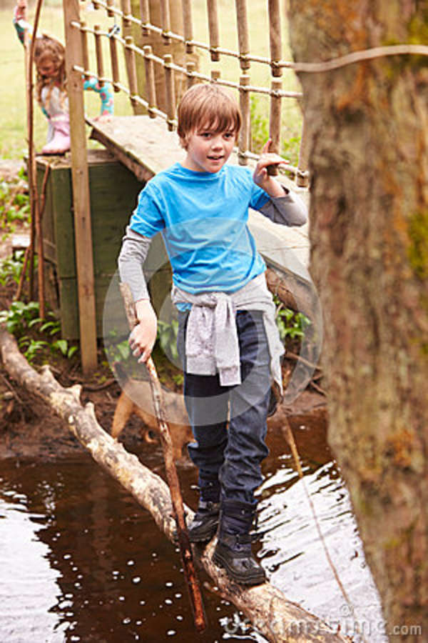 Boy Crossing Stream Balancing On Log At Activity Centre
