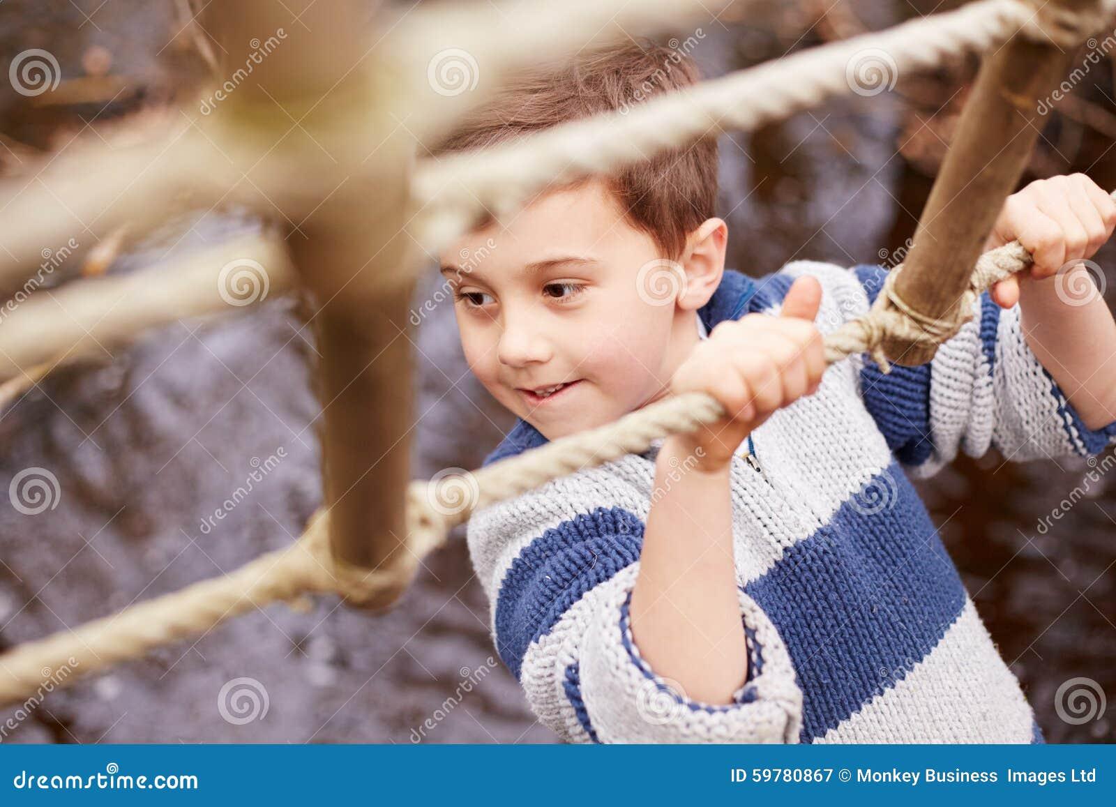 Boy Crossing Stream On Rope Bridge At Activity Centre