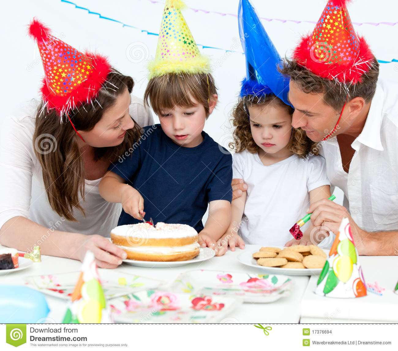 Cute Little Boy Cutting A Birthday Cake For His Family In The Kitchen