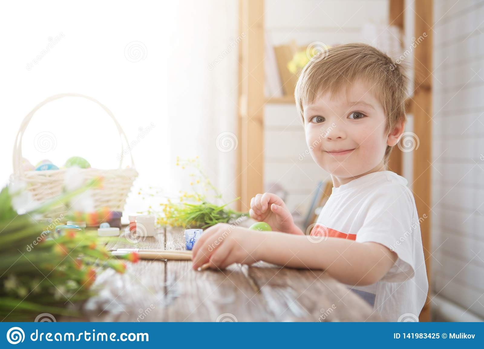 Boy decorate easter egg. A little boy painting and decorating Easter eggs. Portrait of cute boy 3 years old. He holds brush and