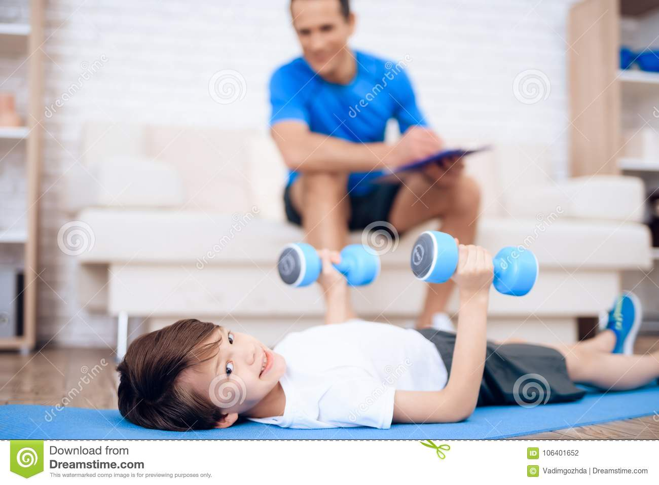 A Boy Is Doing Exercises With Dumbbells On The Floor  Stock Photo