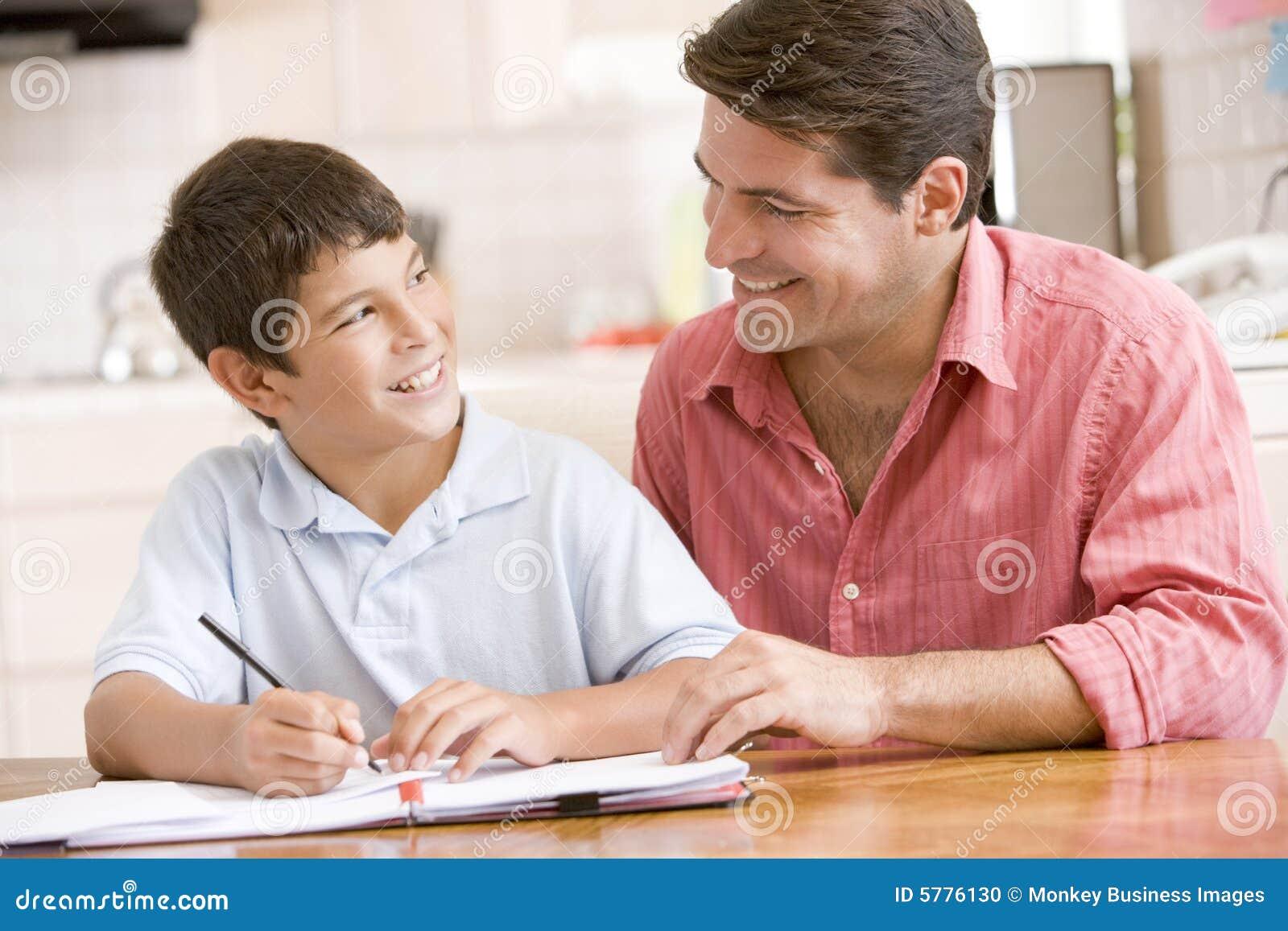 Boy doing helping homework kitchen man young