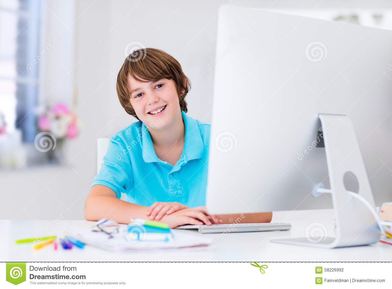 Modern Elementary School Classroom ~ Boy doing homework with modern computer stock photo