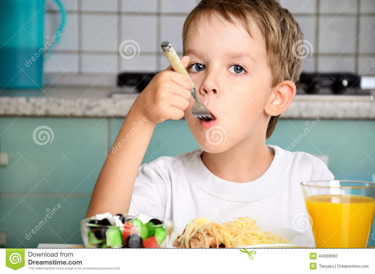 Boy eating with a fork at the table stock photo image for Eating table