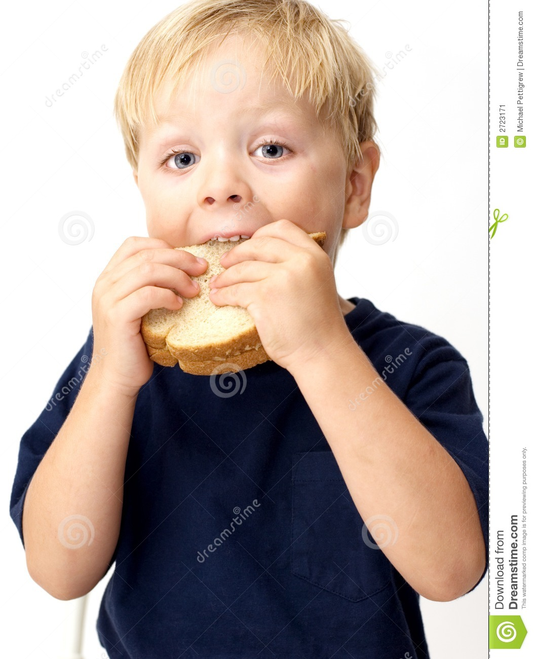 Boy taking a big bite of its peanut butter sandwich.