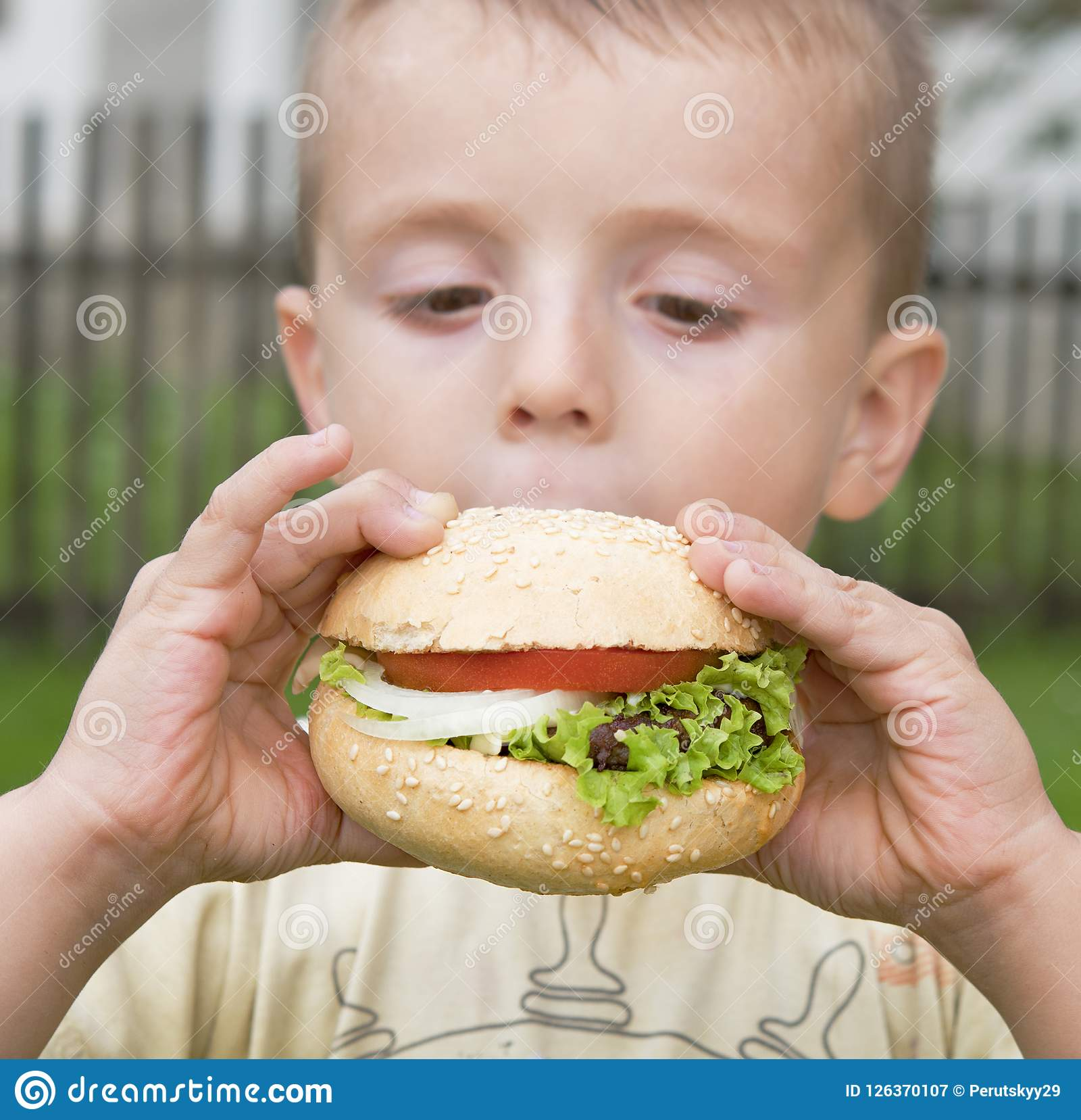 Boy eats hamburger