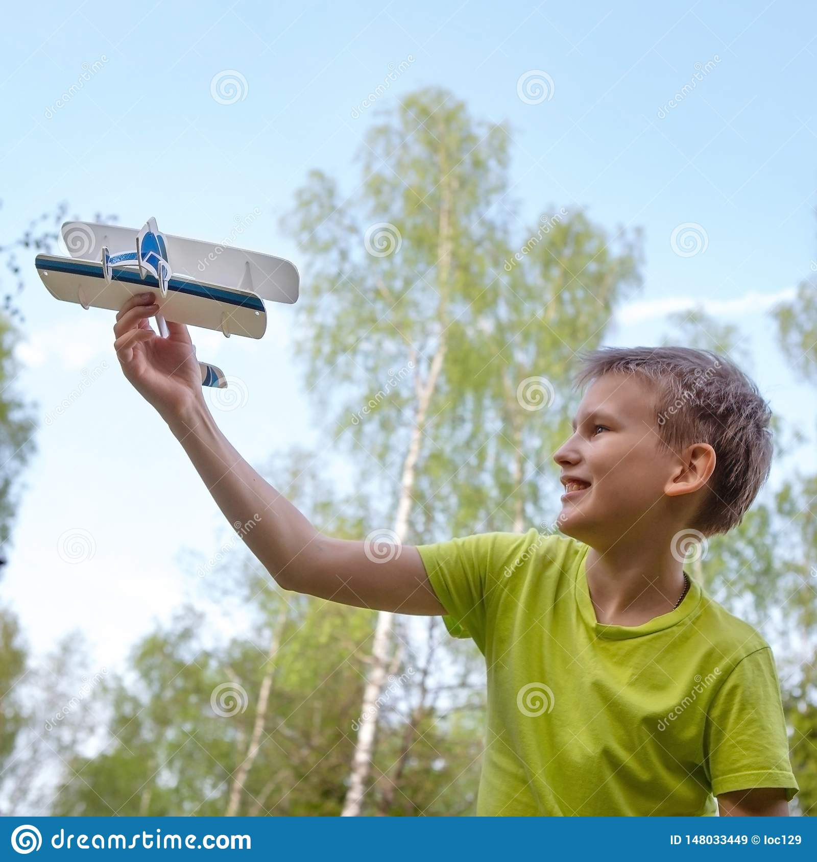 A boy of European appearance with an airplane against the sky with clouds. Bright emotions. Life style