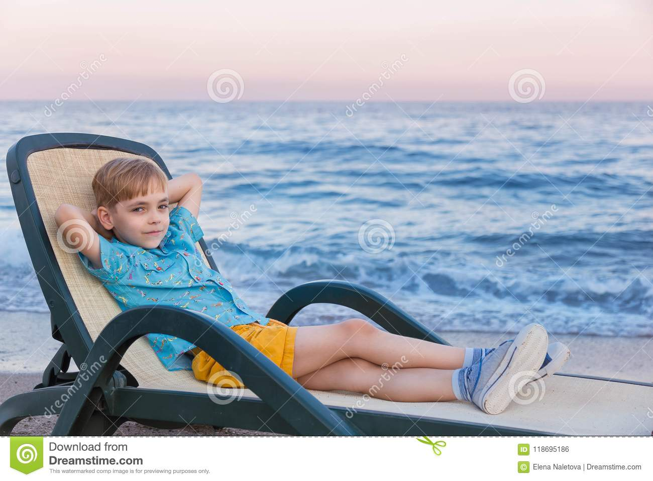 Boy of the European appearance in a blue striped t-shirt of a polo and yellow shorts has a rest in a chaise lounge at a surf strip