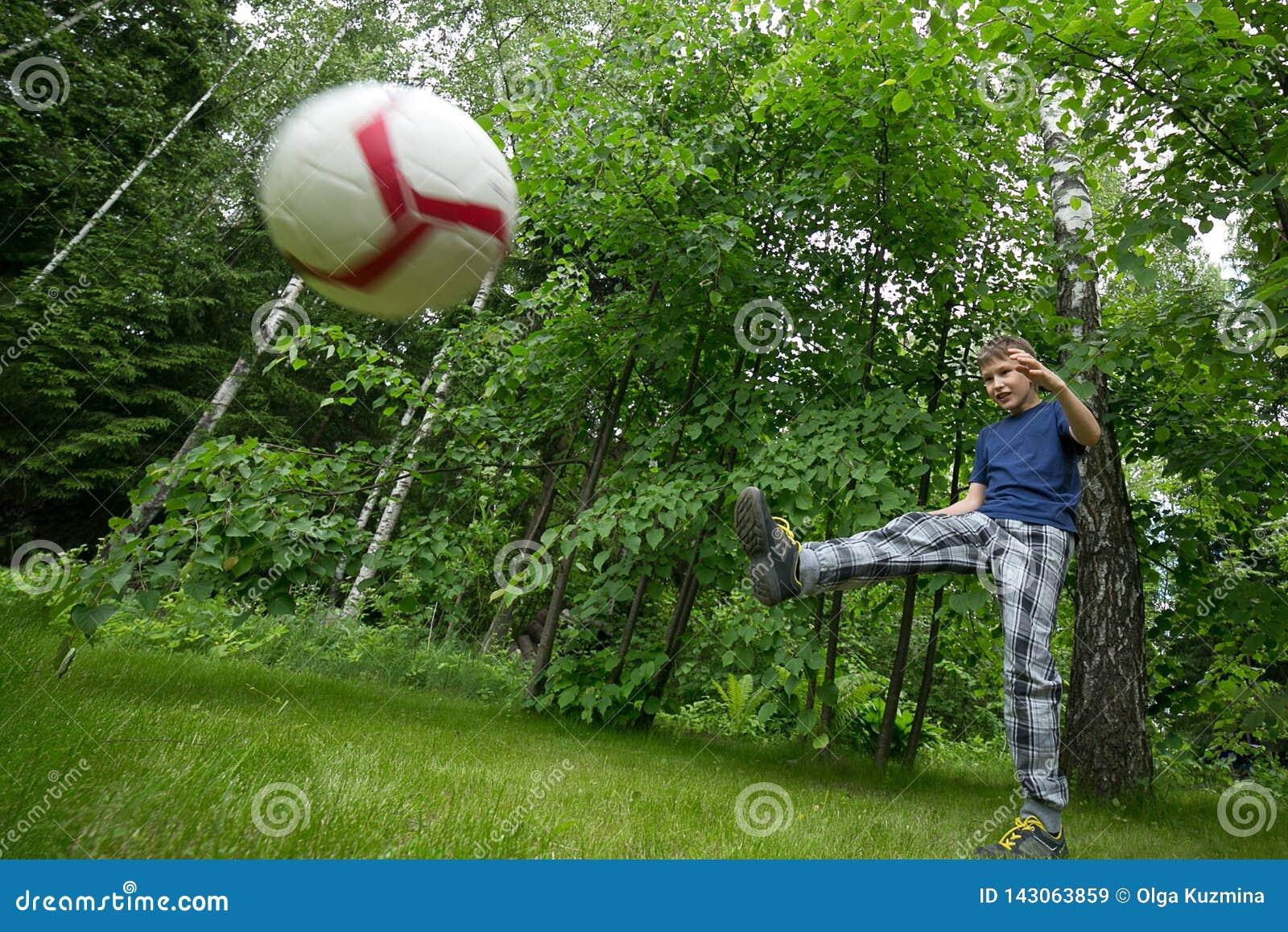 A boy of European appearance plays football. Bright emotion, flying ball