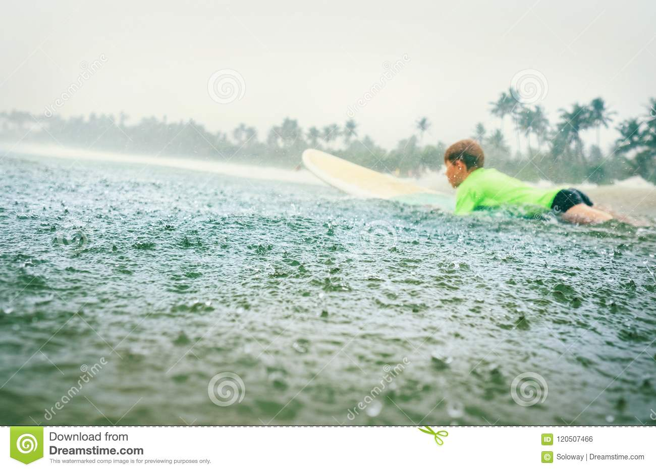 Boy First Step Surfer Learning To Surf Under Tropical Rain