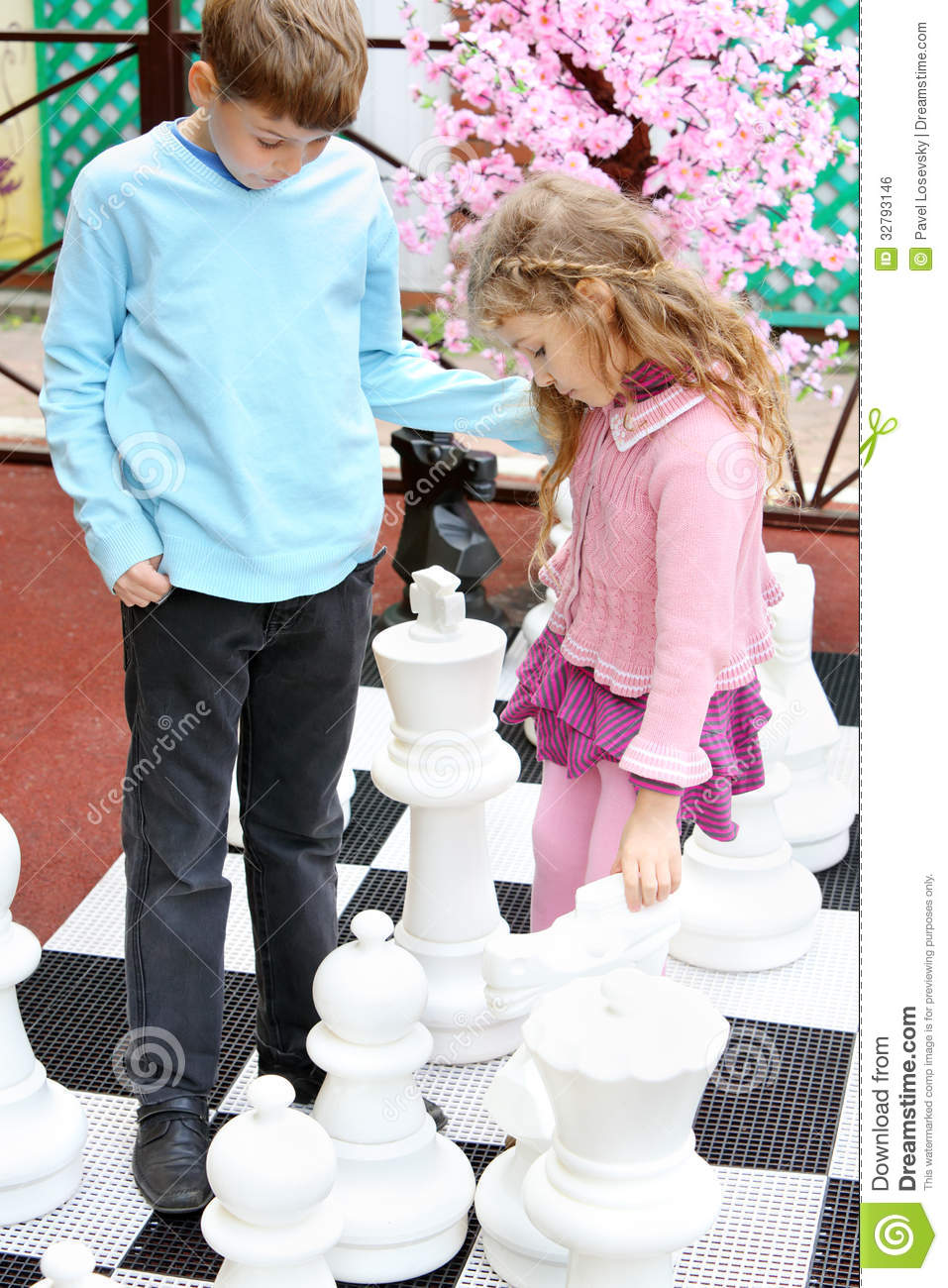 Boy and girl move big chess pieces on big chessboard