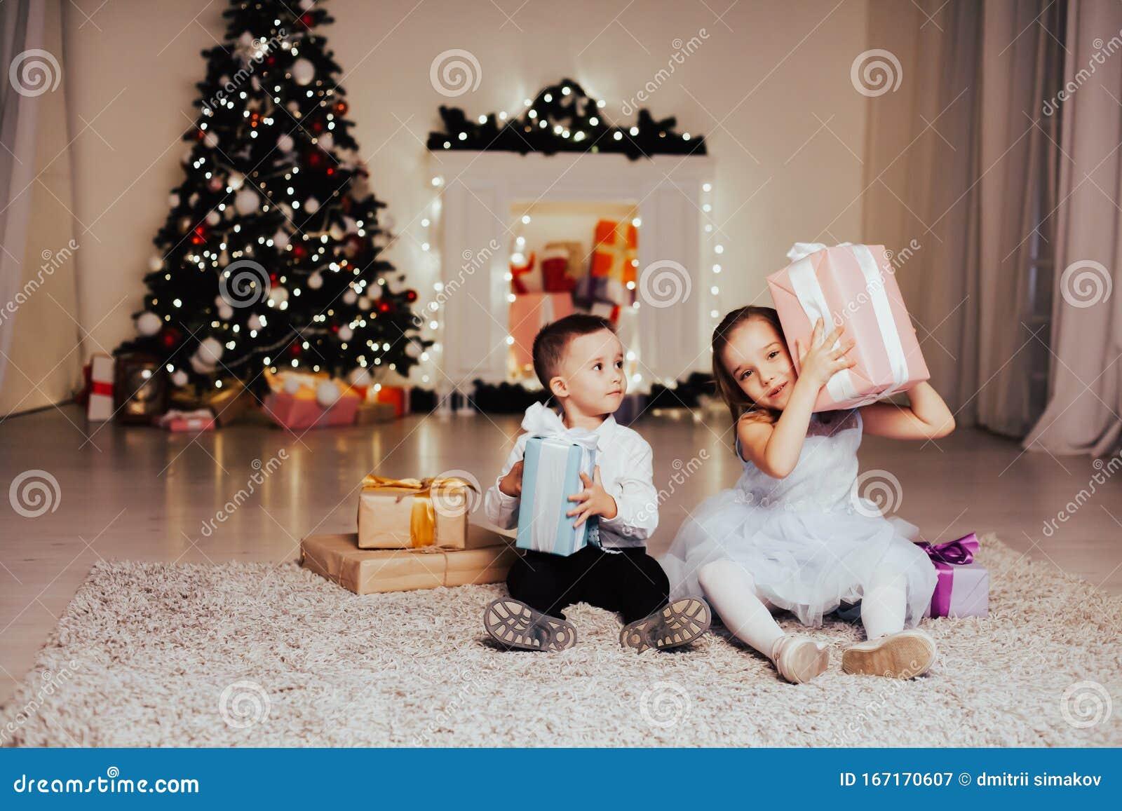 Open Christmas Presents 2020 A Boy With A Girl Open Christmas Presents New Year Holiday Garland