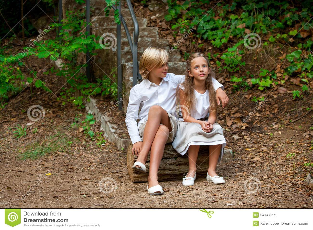 Boy And Girl Sitting On Log In Woods Stock Photography -4094