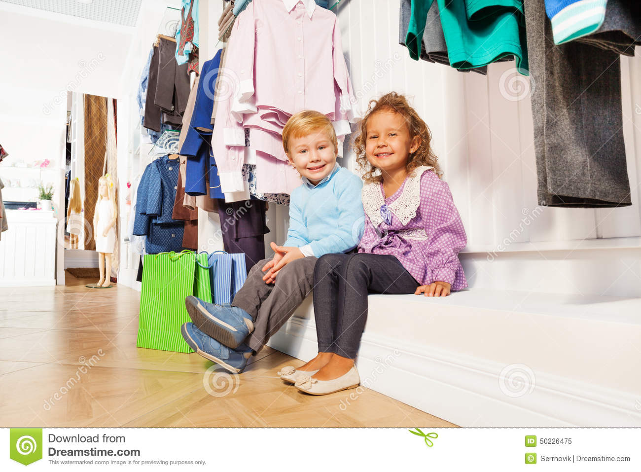 Boy and girl sitting under hangers with clothes stock for Nearby boutiques