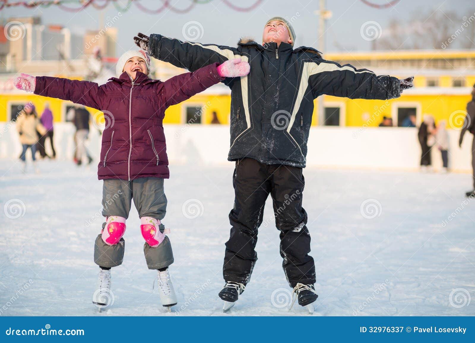 Boy and girl skating on rink