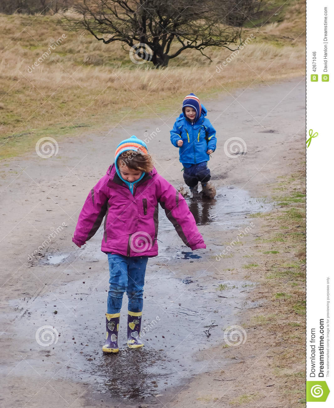 Boy and girl splashing in a muddy puddle