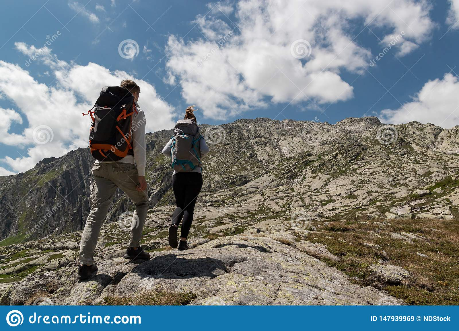 Young couple with big backpack walking to reach the top of the mountain during a sunny day