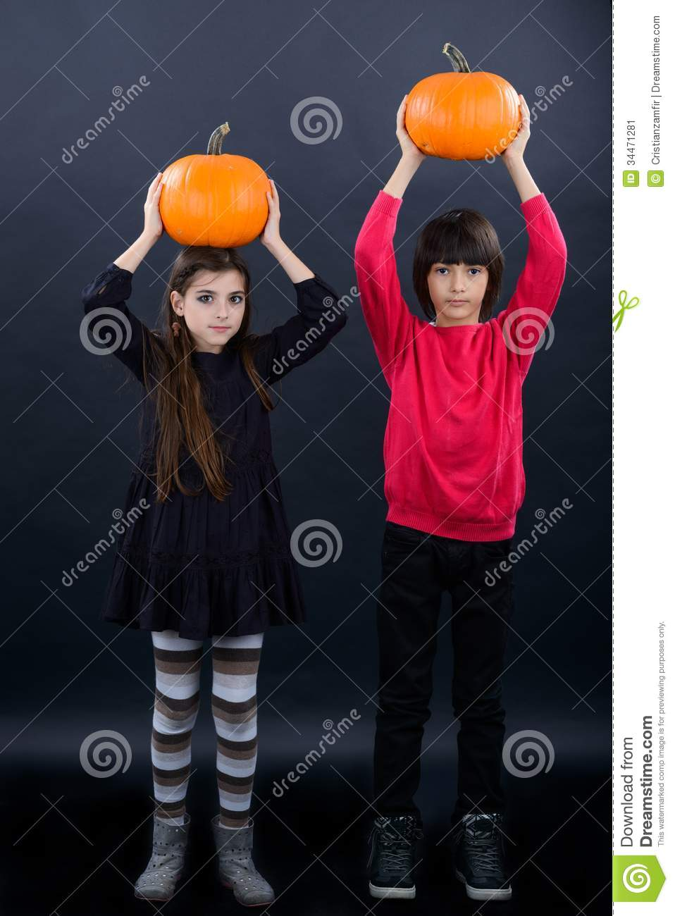 boy and girl wearing halloween costume with pumpkin on black ba