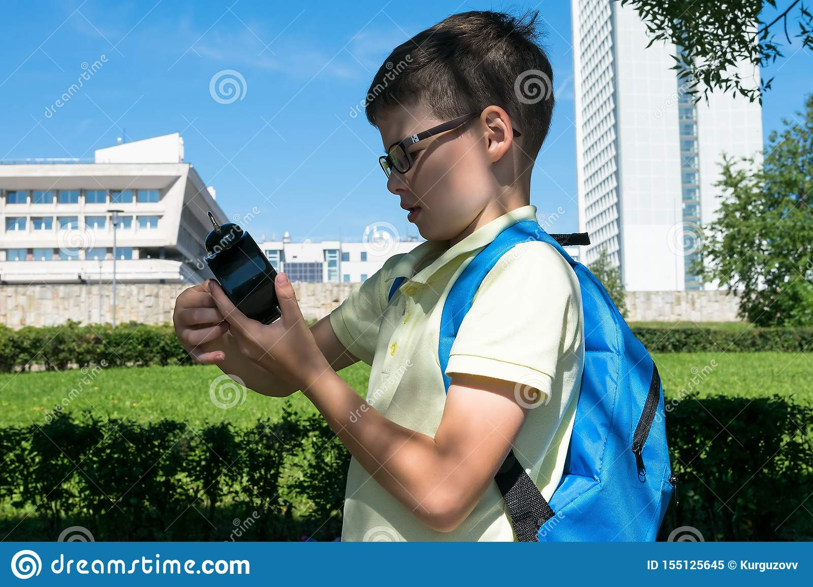A boy in glasses with a backpack on his back looks at his watch before going to school