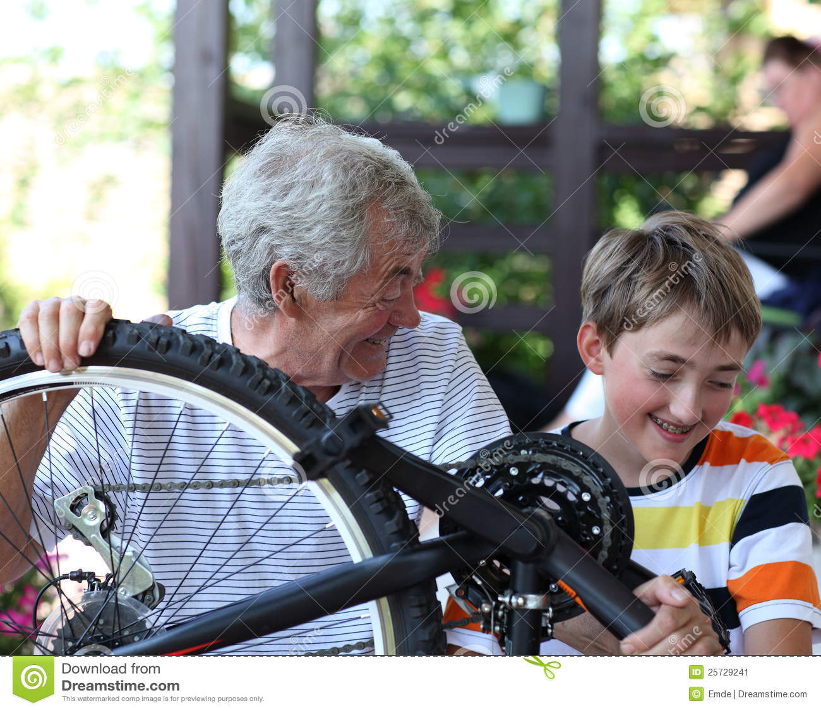 Boy and grandfather fixing bike