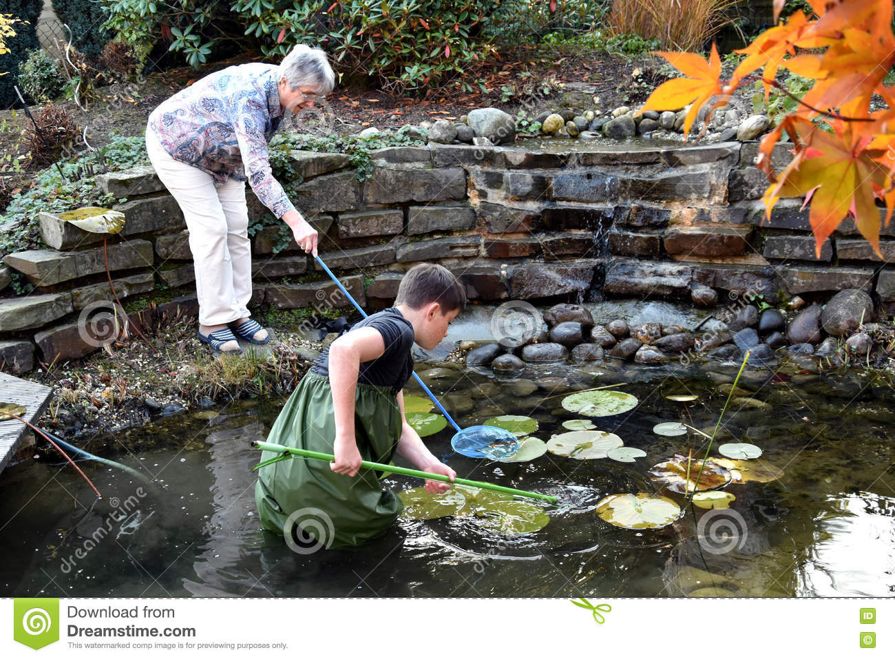Boy and grandmother cleaning garden pond stock photo for Garden pond cleaning