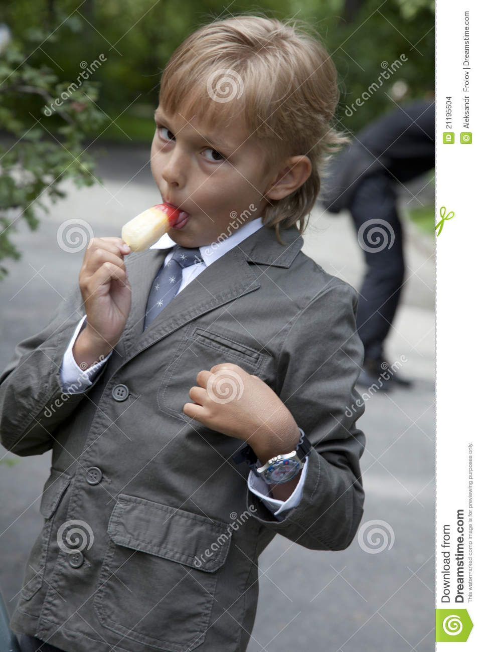Boy in a gray suit eats ice cream
