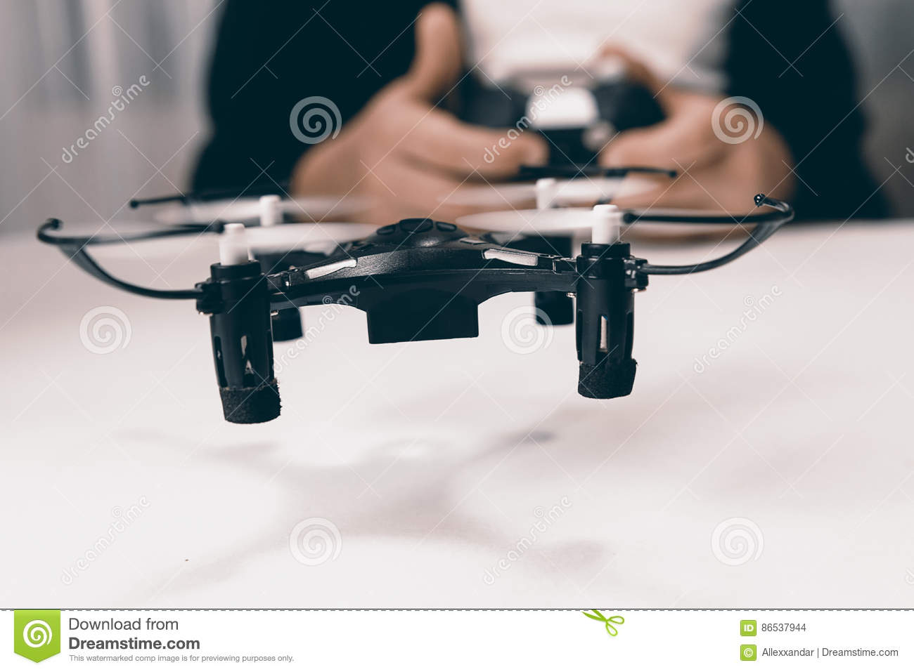 Boy Hands With A Remote Control Flying Small Drone Toy Indoors