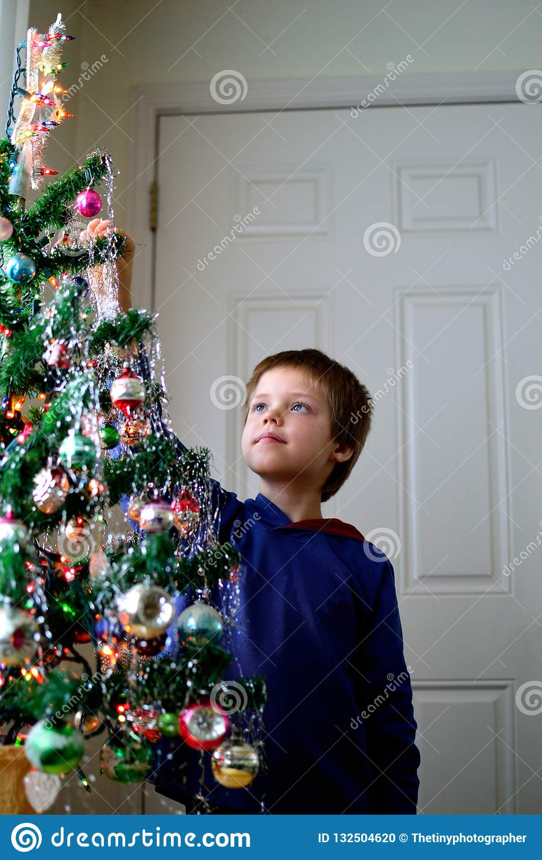Icicles For Christmas Trees.Boy Hanging Icicles On Christmas Tree Decorating Stock Photo