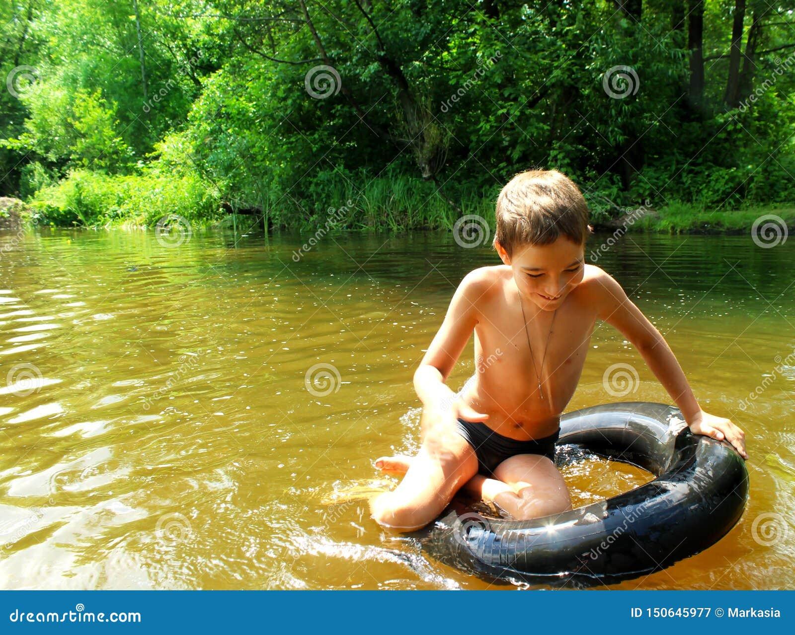 The boy has fun on an tubing in the river.