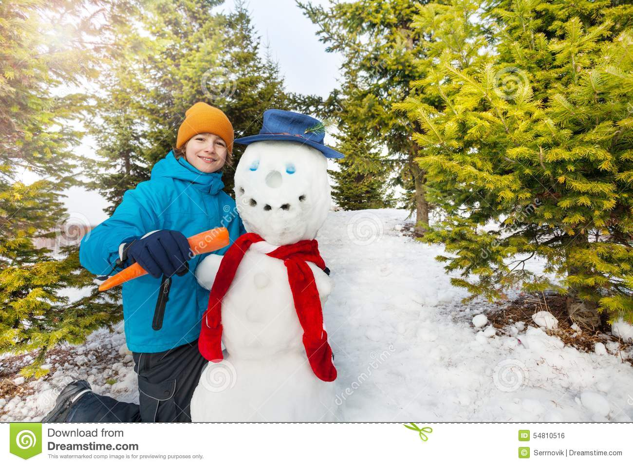 boy holding carrot to put as nose of snowman stock photo